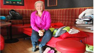 Gill Burns sitting on camp bed in Malone Rugby Club Bar area