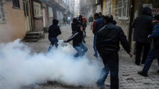 A man starts to throw tear gas as people clash with Turkish police at the Sur district in Diyarbakir, south-eastern Turkey, on January 3, 2016.