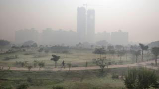 Indian man takes a morning walk in a public garden surrounded by the smog in the outskirts of Delhi, India 20 November 2015.