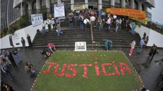 Relatives of the victims of the slaughter of the villa Dos Erres form the word 'Justice' with flowers outside the Supreme Court on August 2, 2011 in Guatemala City before the trial of military men involved.