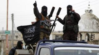 Members of the former Nusra Front gesture as they drive in a convoy touring villages, which they said they have seized control of from Syrian rebel factions, in the southern countryside of Idlib, on 2 December, 2014