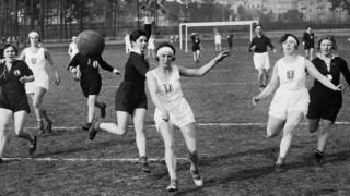 Two groups of women wearing black and white mid-length sportswear enjoy a handball game in a Berlin park 1935.