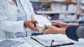 Pharmacist handing over a prescription