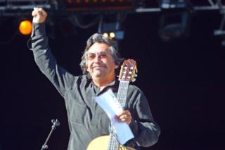 """Ángel Parra con el puño en alto tras cantar durante el festival Fete de l""""Humanite en La Courneuve, cerca de Paris, el 14 de septiembre de 2003."""