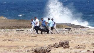 Médicos forenses cargan el cuerpo de uno de los fallecidos tras el accidente.,