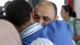 A Tunisian diplomatic staff who was kidnapped along with other colleagues in Libya a week ago, is greeted by a family member after arriving at the airport in Tunis, Tunisia June 19, 2015.