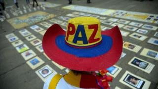 "A person wearing a hat which says ""Paz"" (peace) attends a commemoration for victims of the armed conflict in Colombia"