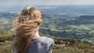 Teenage girl looking out across Northern Ireland landscape
