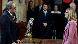 """Catalan regional Government President Quim Torra (L) takes the oath of new Catalan regional Presidency Minister Elsa Artadi (R), during the swearing-in ceremony of the Catalan Government""""s new ministers at the Palau de la Generalitat in Barcelona, northeastern Spain on 2 June 2018."""