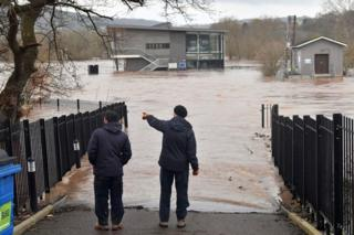 Two men view a flooded area of the sports pavilion at Monmouth School, Monmouth.