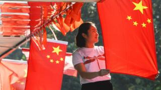A woman hangs Chinese flags in Beijing