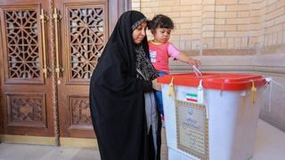 An Iranian woman holds a girl as she casts her vote during a second round of parliamentary elections, in Shiraz, Iran April 29, 2016