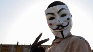 A Sudanese protester wears a Guy Fawkes mask outside the army headquarters in Khartoum on May 6, 2019. - Defiant Sudanese protesters broke their fast on the first day of Ramadan today with chicken soup and beans, vowing to press on with their campaign for a civilian rule. As the call for the evening Maghreb prayer echoed, crowds of protesters gathered at the sit-in area in central Khartoum for iftar after a day of sweltering heat, an AFP correspondent reported.