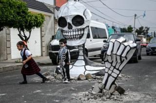 Children pose next to the cardboard skeleton