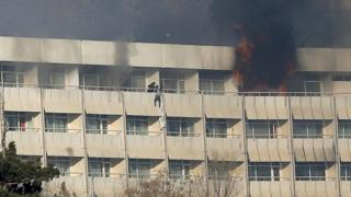A man tries to escape from a balcony at Kabul's Intercontinental Hotel during an attack by gunmen in Kabul, 21 January