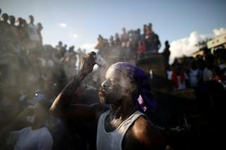 A Voodoo believer covers his face with talcum powder during celebrations in a cemetery in Port-au-Prince, Haiti, 1 November 2018.