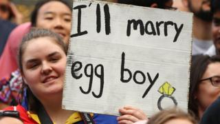 "Seorang pemrotes dalam aksi menuntut mundurnya Senator Australia, Fraser Anning, dan mengajak bersatu melawan rasisme dan Islamofobia, membawa papan kertas yang bertuliskan ""Saya akan menikahi egg boy"", merujuk pada pemuda asal Melbourne, Will Connolly, yang melemparkan telur ke Anning."