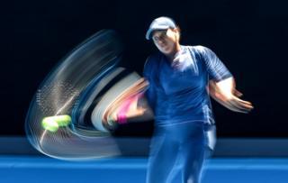 Wir sehen, wie Tennisspielerin Naomi Osaka für einen Ball mit einem Unschärfeeffekt auf dem Foto schwingt