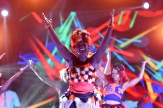 Dancers in matching outfits dance on stage with colourful strobe light behind them.