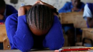 A pupil prays inside a classroom ahead of the primary school final national examinations at a school on Juja road in Nairobi.