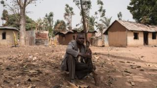 A vigilante sits on the ground with his gun in the village of Bakin Kogi, in Kaduna state, northwest Nigeria, that was recently attacked by suspected Fulani herdsmen