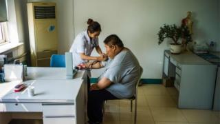 This file photo taken on May 25, 2015 shows a nurse taking the blood pressure of an overweight youth during his acupuncture and exercise treatment at the Aimin (Love the People) Fat Reduction Hospital in the northern port city of Tianjin.