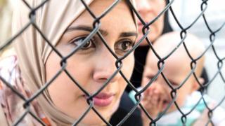 امرأة تنظر خلال حاجز حديدي