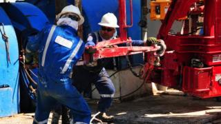 Dos trabajadores en un pozo petrolero