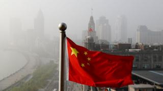 Chinese flag flutters in front of a view of buildings on the Shanghai Bund