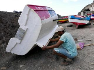 A man mends a boat on the island of Santo Antao.
