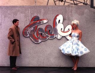 Jools Holland and Paula Yates stood by a wall bearing The Tube logo
