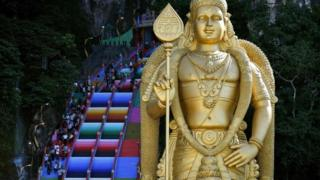 A golden statue stands in front of the colourful stairs at Malaysia's Batu Caves complex