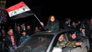 Mujer celebra con una bandera siria