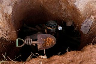 A man emerges from a gold mining pit in Nsuaem-Top, Ghana