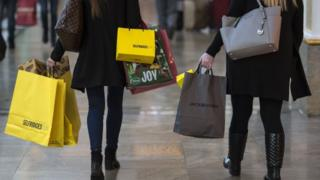 Shoppers carry bags in the Trafford Centre