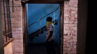 A foreign migrant wears a bandana as he leaves a building in the Kwa Mai Mai area in Johannesburg, on May 10, 2020.