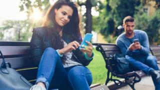 Elinde telefonlarıyla bir kadın ve bir erkek