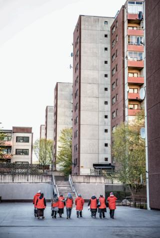 A line of women in red coats make their way through a housing development.