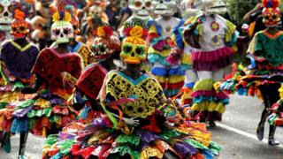 People in colourful dress and skull masks in the parade