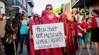 A protester holding a sign demanding protections for women's rights
