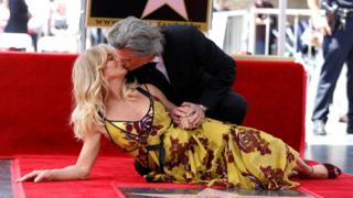 Actors Kurt Russell and Goldie Hawn kiss after unveiling their stars on the Hollywood Walk of Fame in Los Angeles, California