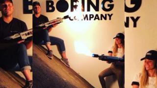 Dos jóvenes aparecen sujetando los lanzallamas y detrás está el aviso de The Boring Company, la empresa de Elon Musk.