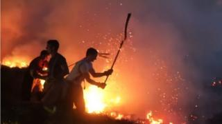 Firefighters try to quell the fire