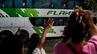 Crianças acenam para pessoas dentro de um ônibus saindo