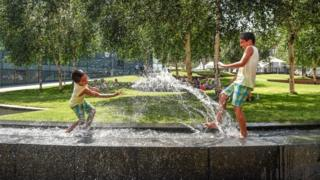 Two boys splash in the water feature beside the National Football Museum in central Manchester