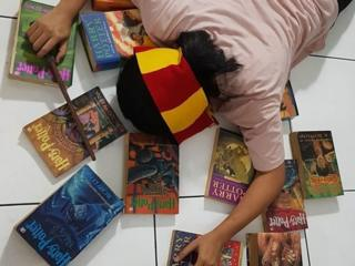 A harry potter fan face down on the floor wearing a hogwarts scarf and surrounded by the books from the series.