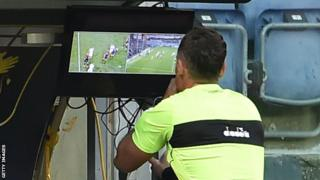 A referee using video technology