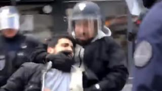 a pixelalted image shows a bearded man wearing a hoody and a riot police helmet grabbing a protester by the neck