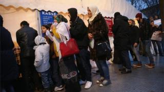 Migrants and refugees wait in the early hours outside Berlin's Central Registration Office for Asylum Seekers of the State Office for Health and Social Services on 9 December 2015