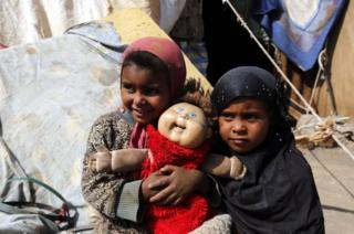 Two children hold their doll